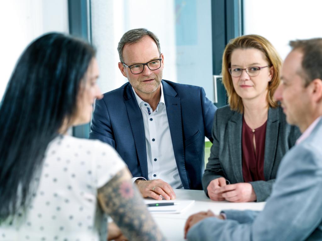 Gruppenfoto Team Wilke Besprechung am Tisch Andreas Wilke